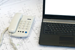 Laptop, phone on project drawings. Working place. White screen royalty free stock images