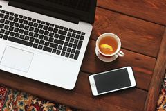 Laptop, phone and tea on wooden background royalty free stock photography