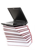Laptop on a pile of books Stock Photo