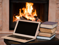 Laptop and pile of books against the background of the fireplace