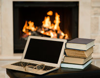 Laptop and pile of books against the background of the fireplace Royalty Free Stock Photo