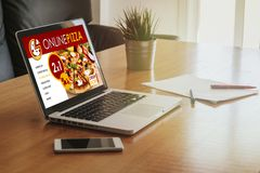 Laptop with pizza shop in the screen, placed on a wooden table. Stock Photos