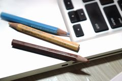Some colored pencils on the laptop. A laptop is placed with three colored pencils on it, isolated on silver background royalty free stock images