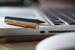 Some colored pencils on the laptop. A laptop is placed with three colored pencils on it, isolated on silver background stock image