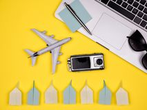 Laptop, plane, camera, pen, notes, keyboard and paper planes. Shot on yellow background on flat lay stock photos