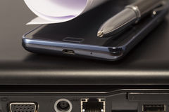 Laptop plug, mobile phone and pen Royalty Free Stock Photography