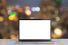 Laptop pokazuje pustego ekran na biurku widzii światła w mieście o obrazy royalty free