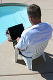 Laptop by pool. Man using a laptop poolside stock image