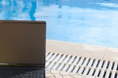 Laptop by  the pool, work on holiday concept Royalty Free Stock Photos