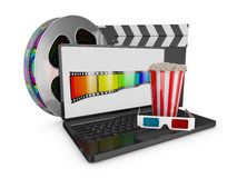 Laptop and popcorn. Reel of film, clapperboard and a laptop on which the popcorn and 3D glasses Royalty Free Stock Photo