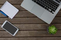 Laptop, potteninstallatie, blocnote, pen en mobiele telefoon op houten plank royalty-vrije stock afbeeldingen