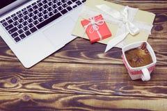 Laptop, prezenty i filiżanka kawy z, cynamonem i anyżem na drewnianym tle Zdjęcie Stock
