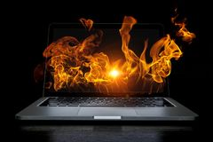 Laptop problem or break. Mixed media. Open laptop with fire flames coming from screen on dark background. Mixed media Stock Images
