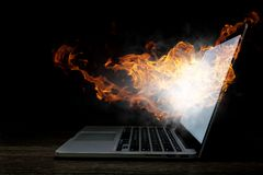 Laptop problem or break. Mixed media. Open laptop with fire flames coming from screen on dark background. Mixed media Royalty Free Stock Photo