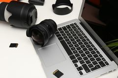 Laptop and professional photographer`s equipment. On table stock images