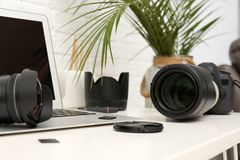 Laptop and professional photographer`s equipment. On table indoors royalty free stock photos
