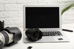 Laptop and professional photographer`s equipment on table indoors. Space for text stock photos
