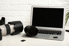 Laptop and professional photographer`s equipment on table indoors. Space for text royalty free stock photos