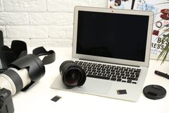 Laptop and professional photographer`s equipment. On table indoors. Space for text stock photo