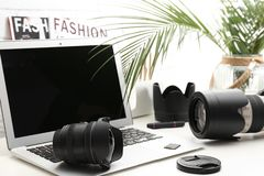 Laptop and professional photographer`s equipment. On table indoors. Space for text royalty free stock image