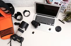 Laptop and professional photographer`s equipment. On table, top view. Space for text royalty free stock photography