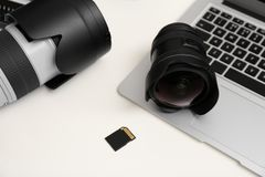 Laptop and professional photographer`s equipment. On white table stock image