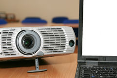 Laptop with the projector on office table Stock Photo