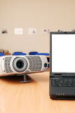 Laptop with the projector on office table Stock Image