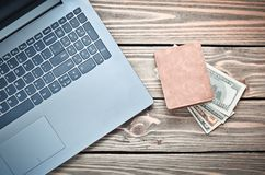 Laptop and a purse with money on a wooden table. The concept of online work on the Internet, freelancing. Top view royalty free stock images