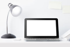 Laptop and reading lamp at desk with scrap paper on the wall Stock Image