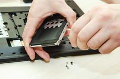 Laptop reparatie, close-up van handen met een schroevedraaier stock fotografie