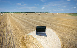 Laptop on rolled bale on field Royalty Free Stock Photos