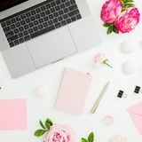 Laptop, roses flowers, diary, pen, envelope and petals on white background. Business concept. Flat lay. Top view royalty free stock photo