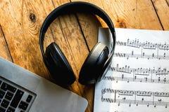 Laptop, słucha muzyka, na hełmofonie chłodzi z espres Obraz Stock