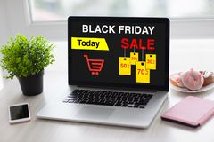Laptop with sale black friday on screen and phone. In the office Royalty Free Stock Photo