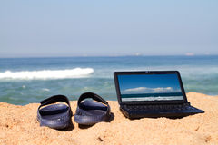 Laptop and sandals on beach Stock Images
