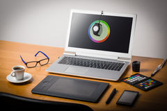 Laptop screen calibtation. Photographer's workspace with calibrator or profiler attached to laptop's display to get accurate colors Royalty Free Stock Image