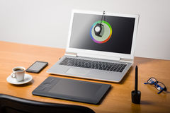 Laptop screen calibtation. Photographer's workspace with calibrator or profiler attached to laptop's display to get accurate colors Stock Image
