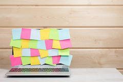Laptop screen covered in blank sticky notes Stock Photo