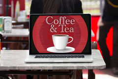 Laptop screen showing a message on the screen coffee and tea cup Royalty Free Stock Photo
