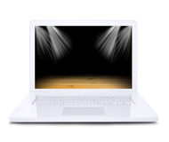 On the laptop screen shows a wooden floor floodlit. White background royalty free stock photography