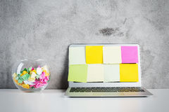 Laptop screen with stickers. Creative desktop with colorful stickers covering laptop screen and decorative glass bowl on concrete background. Mock up stock image