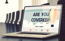 Laptop Screen with Are You Covered Concept. 3d. Are You Covered Concept. Closeup Landing Page on Mobile Computer Display on Background of Conference Hall in Royalty Free Stock Photography