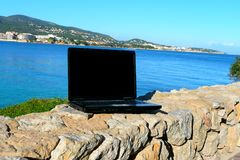 Laptop by the sea. An open laptop computer on a wall overlooking the sea Royalty Free Stock Photography