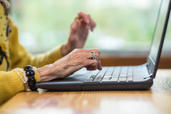Laptop and senior woman`s hands. Notebook pc on a desk. Getting familiar with modern technologies stock photos