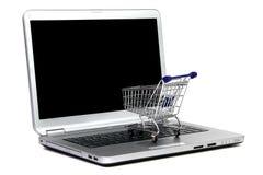 Laptop and shopping cart Royalty Free Stock Photos