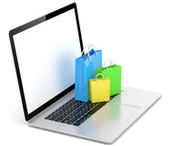 Laptop and  shopping pags on white Royalty Free Stock Images
