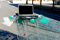Laptop and shopping trolleys stock photo