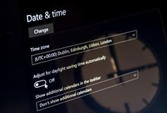 Laptop showing dayligt saving time menu with a clock reflected on the screen. UTC 00 royalty free stock images