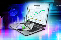 Laptop showing a spreadsheet and a paper with statistic charts Royalty Free Stock Photo